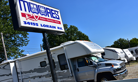 picture of Moores RV front sign and a line of rvs for sale, moores rv